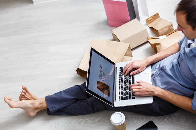 Startupowy mały biznes przedsiębiorca z laptopem, niezależny człowiek pracujący w pudełku, młody azjatycki właściciel firmy w domowym biurze, opakowanie i dostawa do marketingu online, koncepcja dostawy dla mśp