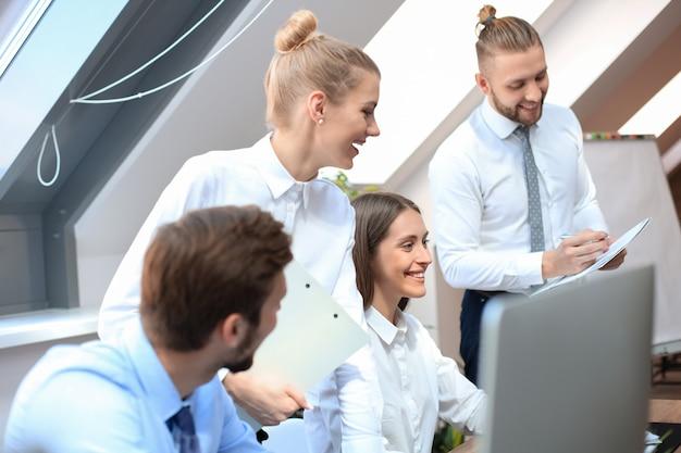 Startupowy zespół biznesowy na spotkaniu w burzy mózgów w nowoczesnym, jasnym wnętrzu biurowym, pracujący na komputerach typu tablet i pc.