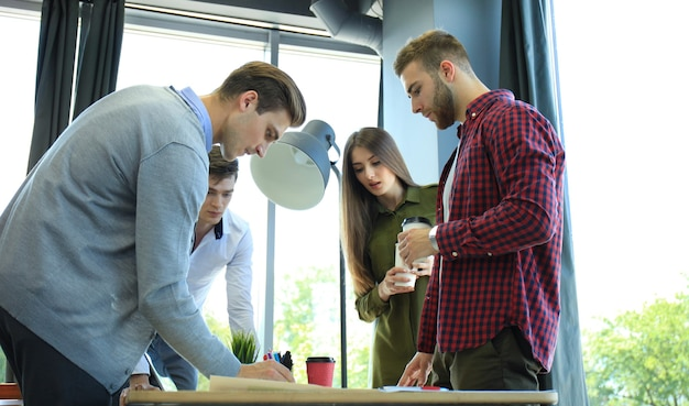 Startupowy zespół biznesowy na spotkaniu w nowoczesnym, jasnym wnętrzu biurowym, burza mózgów, pracująca na laptopie i tablecie