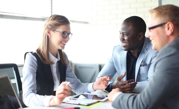 Startupowy zespół biznesowy na spotkaniu w nowoczesnym, jasnym wnętrzu biurowym, burza mózgów, pracujący na laptopie i tablecie