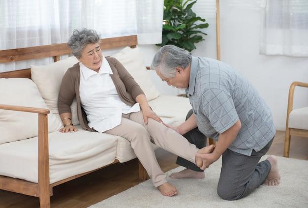 Staruszek opiekuje się starszą kobietą po urazie nogi