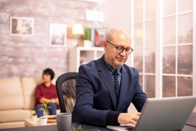 Staruszek po sześćdziesiątce pracuje na laptopie w przytulnym salonie, podczas gdy jego żona jest w tle