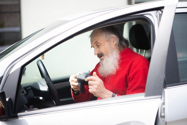 Staruszek senior z siwą brodą siedzi w samochodzie i trzyma aparat fotograficzny