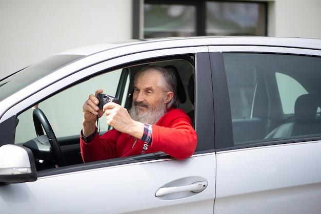 Staruszek senior z siwą brodą siedzi w samochodzie i trzyma zabytkowy aparat fotograficzny