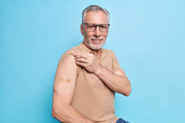 Staruszek z siwymi włosami pokazuje zaszczepione ramię motywuje do zaszczepienia się przeciwko koronawirusowi, aby zatrzymać epidemię, troszczy się o zdrowie w jego wieku, nosi okulary w brązowym t-shirtie, odizolowane na niebieskiej ścianie