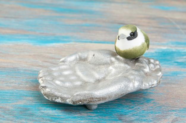 Stary aluminiowy karmnik dla ptaków, miska do picia dla ptaków, ozdobna miska na ręce na niebieskim tle drewnianych. skopiuj miejsce na tekst, rekwizyty fotograficzne.
