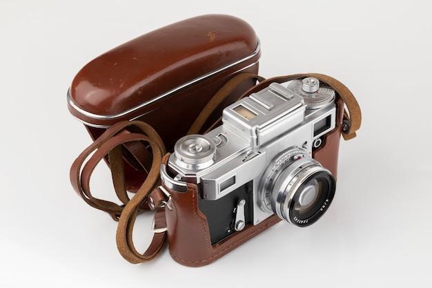 Stary aparat filmowy w brązowym skórzanym etui na białym tle z bliska