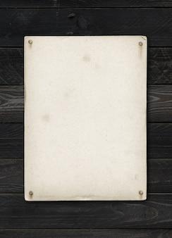 Stary arkusz papieru z teksturą przybity na stole z czarnego drewna. makieta pionowa