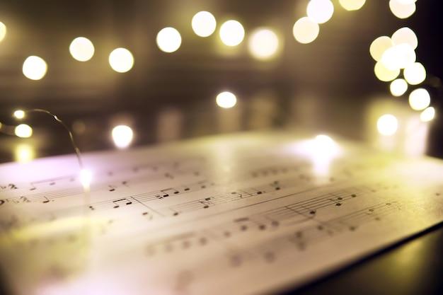 Stary arkusz z nutami muzyki boże narodzenie jako tło przed niewyraźne światła. koncepcja muzyki świątecznej