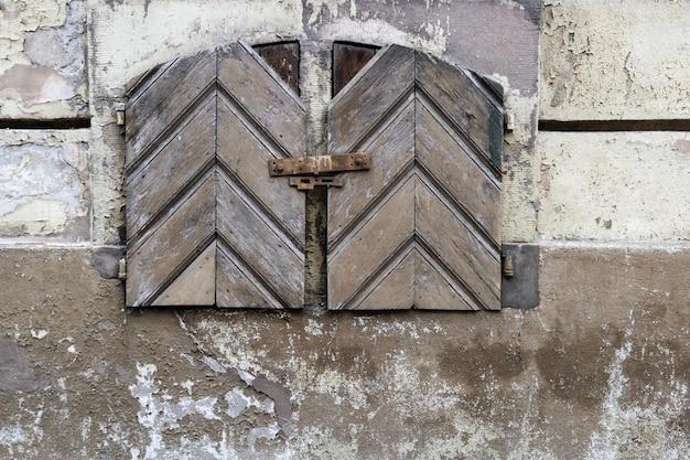 Stary betonowej ściany tło z krakingową farbą z drewnianym rocznikiem, zamykający drzwi. część starego budynku.
