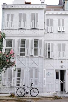Stary biały budynek z zaparkowanym rowerem