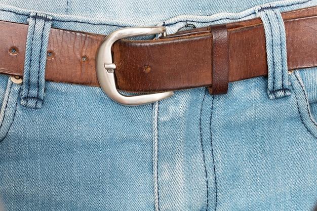 Stary brązowy pasek z niebieskimi dżinsami.