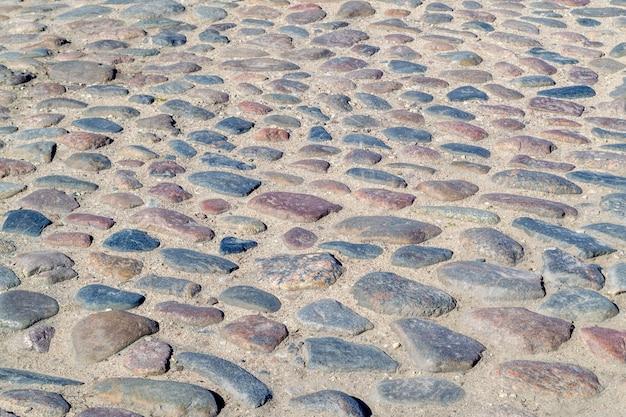 Stary bruk. okrągłe kamienie brukowe na ulicy. droga z kamieni