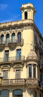 Stary budynek mieszkalny w słoneczny dzień w barcelonie, hiszpania. ujęcie pionowe
