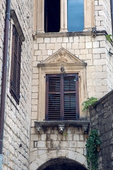 Stary budynek w czarnogórze z oknami i okiennicami i bluszczem