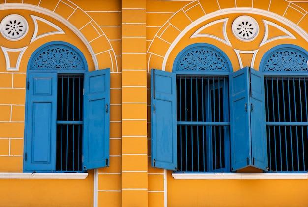 Stary budynek z niebieskim oknem i żółtymi budynkami