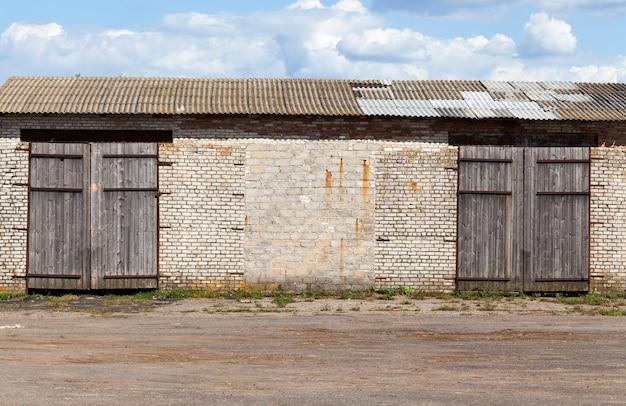 Stary ceglany magazyn z dużymi zamkniętymi bramami, błękitne niebo