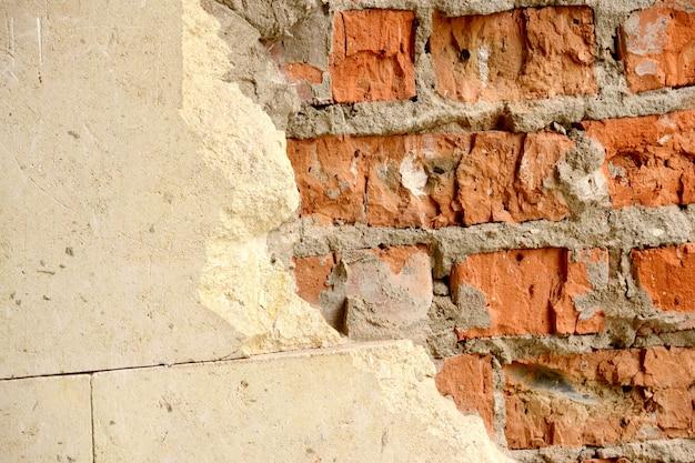 Stary ceglany mur z poziomymi, częściowo wyszczerbionymi białymi płytkami