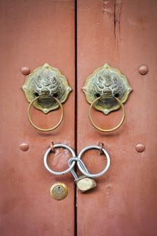Stary chiński lew klamka i kłódka na blisko brązowym tle drewnianych drzwi