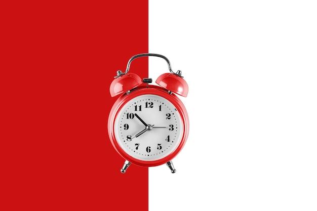 Stary czerwony budzik na ścianie czerwony i biały. kreatywne mieszkanie leżał vintage zegar na kolorowej ścianie, kopiuj przestrzeń w minimalistycznym stylu, pusty szablon tekstu