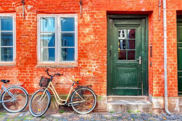 Stary czerwony dom w centrum kopenhagi z rowerem. stara średniowieczna dzielnica w kopenhadze, dania.