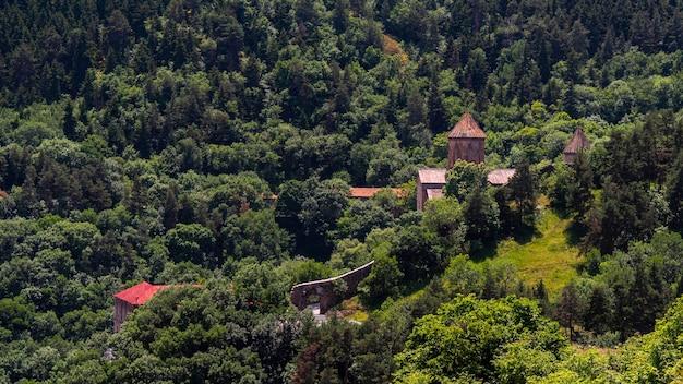 Stary czerwony kościół zagubiony w górskim lesie. starożytny gruziński klasztor chrześcijański