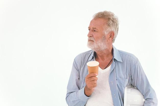 Stary człowiek amerykański pracownik rasy kaukaskiej ręka trzyma papierowy kubek kawy na sobie ubranie dorywczo relaks, patrząc od hotelu odizolowane