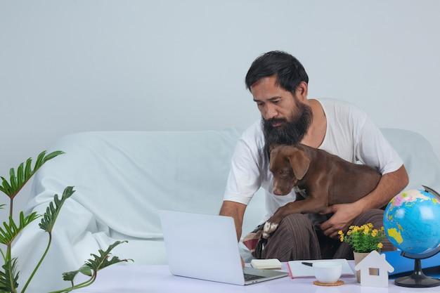 Stary człowiek bawi się ze zwierzakiem podczas pracy na kanapie w domu.