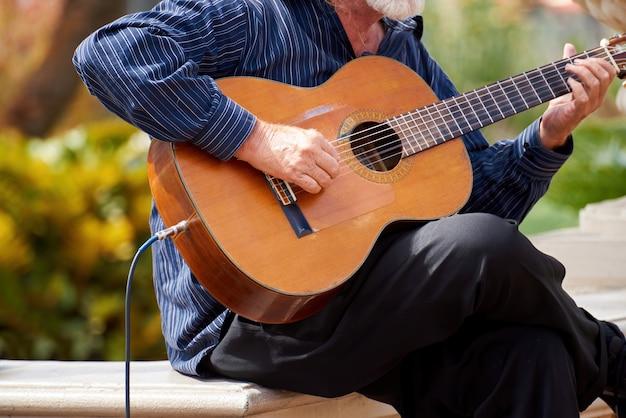 Stary człowiek bawić się gitarę outside w ogródzie