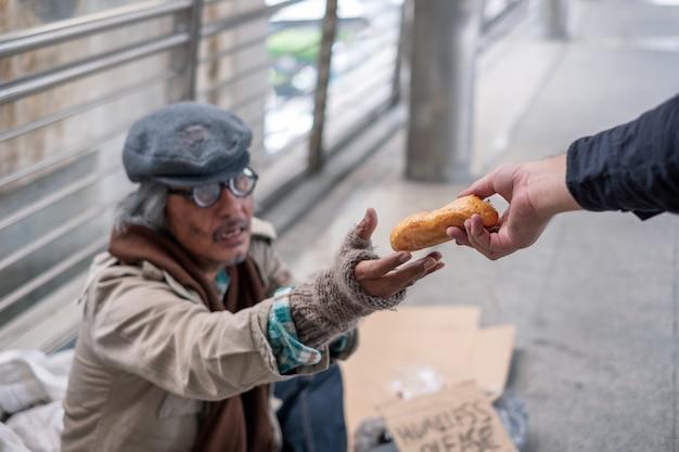 Stary człowiek bezdomny sięga po chleb od dawcy na moście na korytarzu
