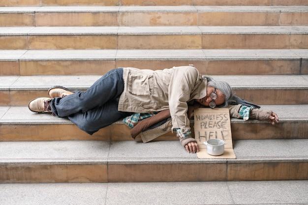 Stary człowiek bezdomny śpi na schodach w mieście