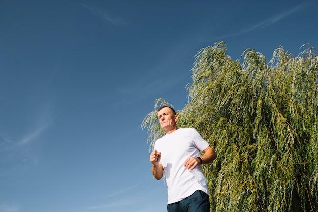Stary człowiek biega outdoors niskiego kąta widok