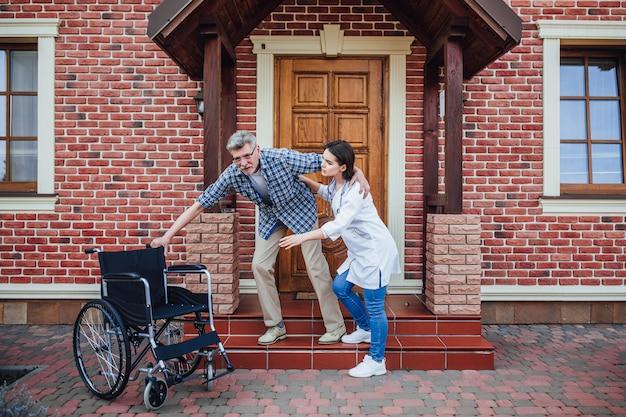 Stary człowiek chce usiąść przy swoim krześle obok domu opieki