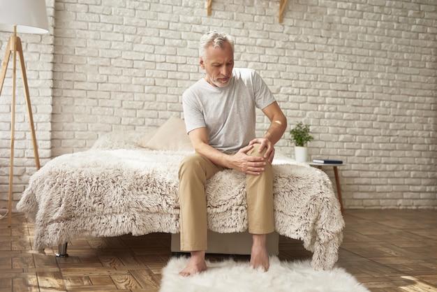 Stary człowiek cierpi na ból stawu kolanowego w sypialni.