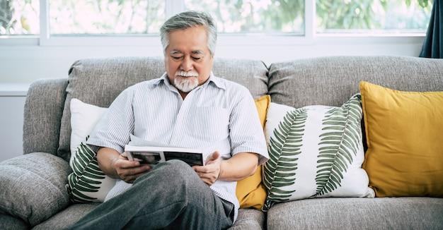 Stary człowiek czyta w salonie