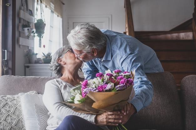 Stary człowiek daje kwiaty swojej żonie siedzącej na kanapie w domu na dzień san valentines. emeryci i renciści cieszą się niespodzianką, całując się razem. zakochani ludzie bawią się.