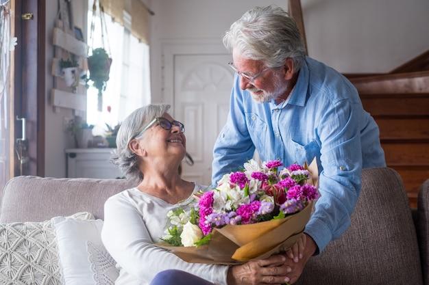 Stary człowiek daje kwiaty swojej żonie siedzącej na kanapie w domu na dzień san valentines. emeryci i renciści wspólnie cieszą się niespodzianką. zakochani ludzie bawią się.