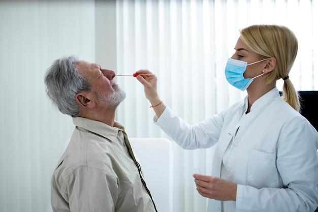 Stary człowiek dostaje test pcr w gabinecie lekarskim podczas epidemii wirusa koronowego