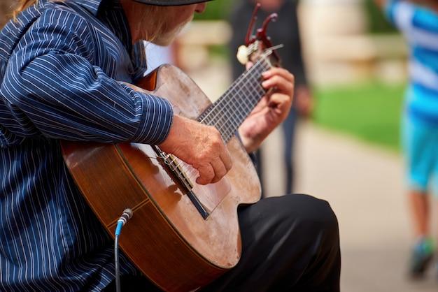 Stary człowiek gra na gitarze na ulicy