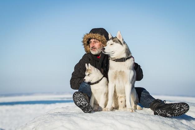 Stary człowiek i psy zaprzęgowe na krze.