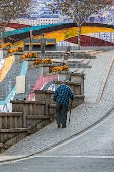 Stary człowiek idzie na ulicy