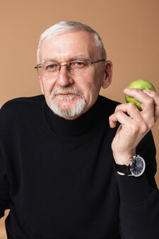 Stary człowiek jedzenie jabłka portret