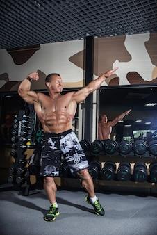 Stary człowiek jest na siłowni w pobliżu hantli, treningu siłowego. sportowiec na siłowni utrzymuje formę fizyczną. mężczyzna emeryt z dużymi mięśniami i idealną prasą.