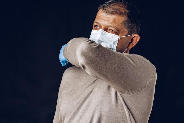 Stary człowiek jest ubranym ochronną maskę i rękawiczki na zmrok ścianie