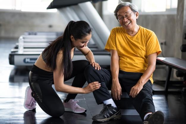 Stary człowiek masaż nóg przez dziewczynę w siłowni