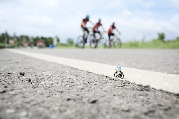 Stary człowiek miniaturowy na przejażdżkę rowerem w wiejskiej drodze z grupą tła wyścigu rowerowego.