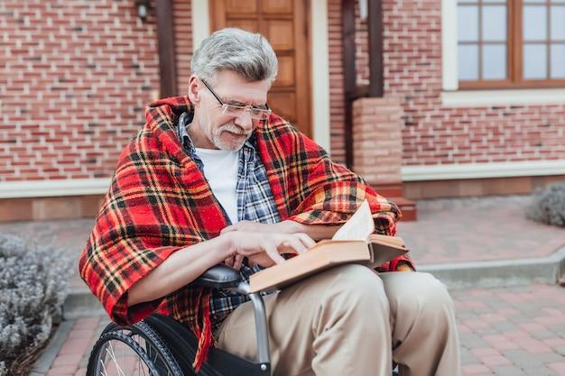 Stary człowiek na wózku inwalidzkim, czytający ciekawą powieść i pozujący do kamery blisko domu opieki