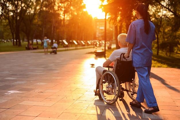 Stary człowiek na wózku inwalidzkim i pielęgniarka chodzą po parku