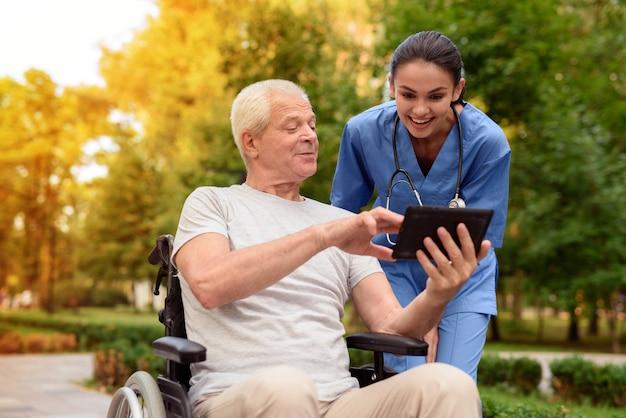 Stary człowiek na wózku inwalidzkim z dumą pokazuje szczęśliwą pielęgniarkę.