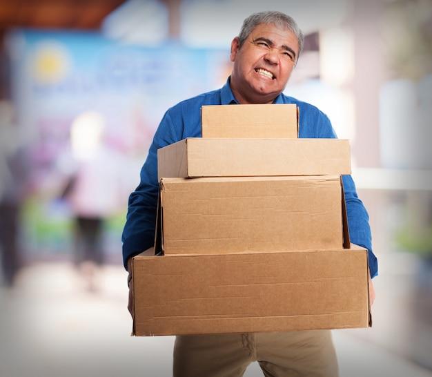 Stary człowiek niosący wiele pudeł tekturowych